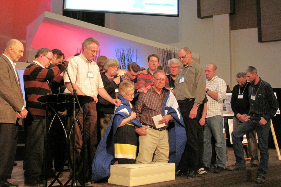 Representatives from each SKMB church surround Ralph and Grace Gliege with a memorial quilt and their prayers in recognition of Gliege's retirement. (Photo by Karla Braun)